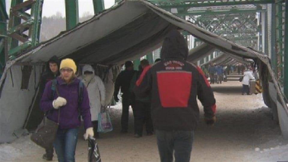 Les citoyens circulent sous une série de tentes sur le pont Sainte-Anne.
