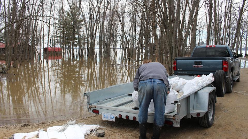 Un résident transporte des sacs de sable dans son véhicule.