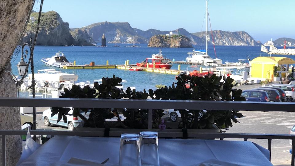 Vista della soleggiata baia di Ponza da un tavolo in ombra.