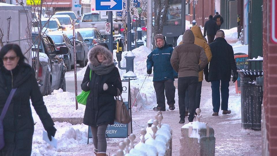 En hiver, différentes personnes marchent sur un trottoir de Moncton.