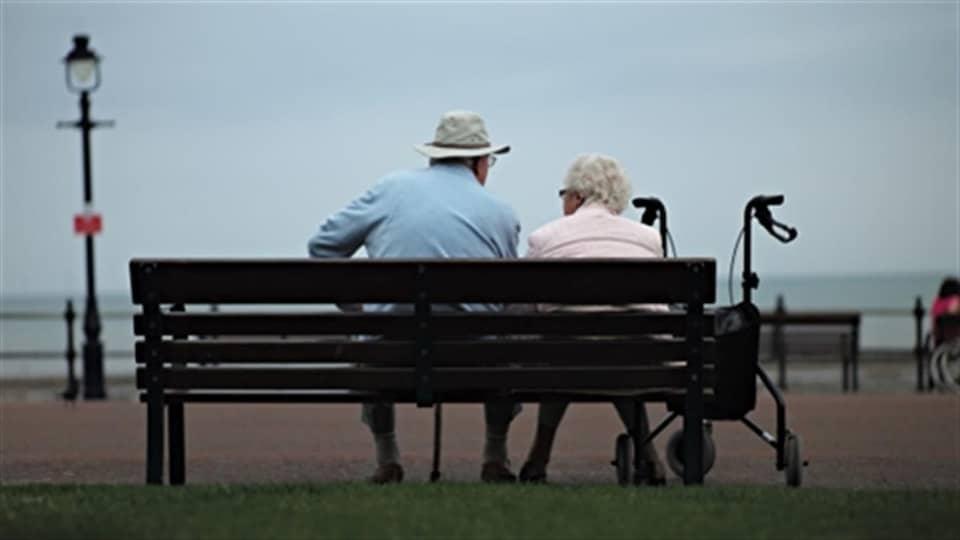 Deux personnes âgées sont assises sur un banc, de dos.