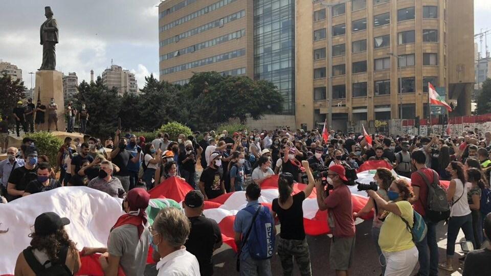Des dizaines de Libanais rassemblés autour d'un drapeau au milieu d'une place publique.