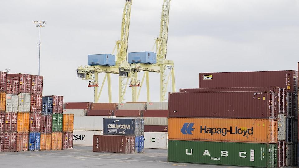 De grands conteneurs sont empilés dans une cour extérieure du port de Montréal. La place est déserte.