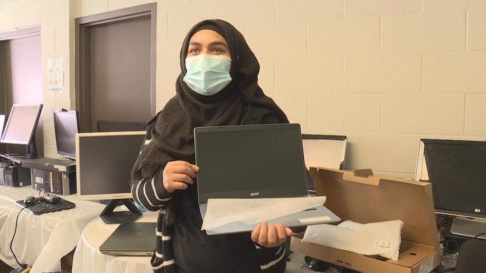 Une jeune femme tient un ordinateur.