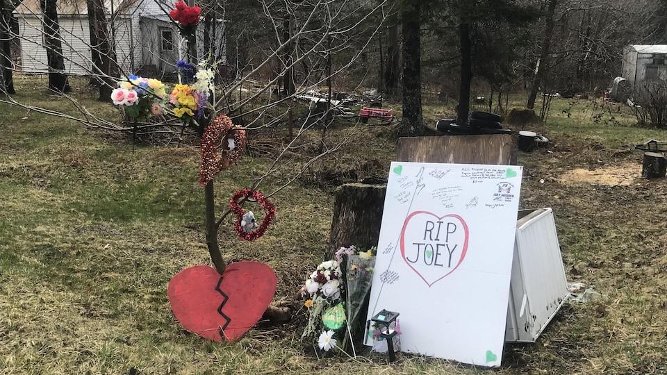 Des gens ont disposé des fleurs et écrit des messages sur une affiche devant la maison.