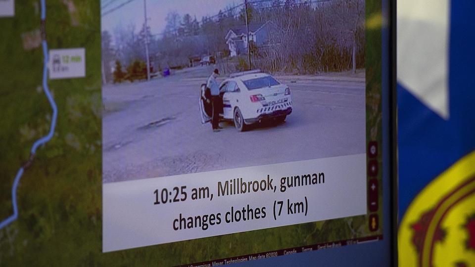 Une photo présentée sur un écran montre un homme en train de retirer une veste de police, près de ce qui ressemble en tout point à une voiture de la GRC, sur le bord d'une route rurale.
