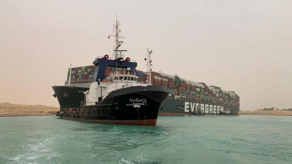 Des remorqueurs tentent de débloquer un porte-conteneurs échoué dans le canal de Suez.