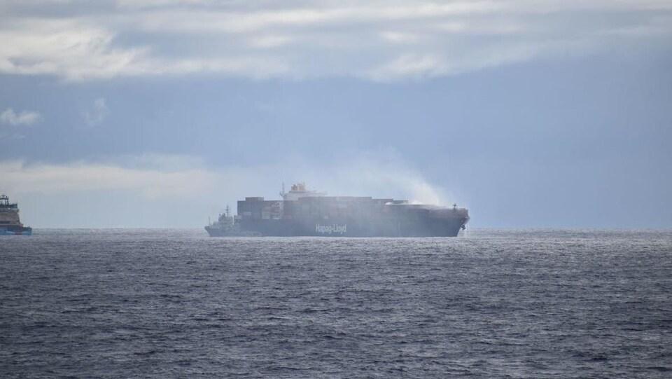 Un panache de fumée blanche s'élève des conteneurs à l'avant du navire.
