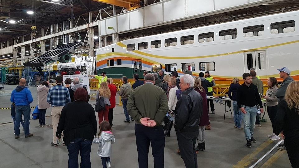 Une foule qui visite une usine de construction de wagons de trains.