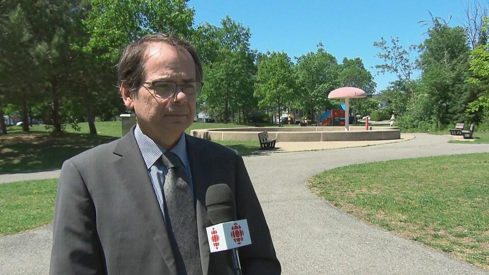 Mario Vaillancourt est devant un micro de Radio-Canada et regarde la journaliste.