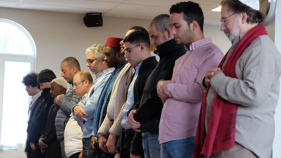 Une dizaine d'hommes sont enlignés, yeux fermés et mains jointes.