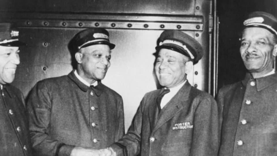 Quatre hommes en uniforme de porteurs dans un train.