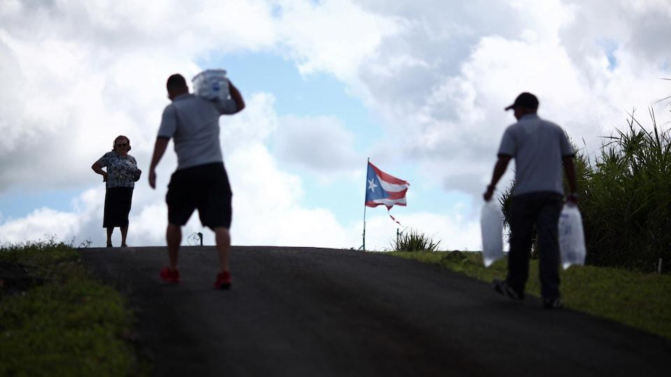 Une femme attend pendant que des employés municipaux distribuent l'eau et la glace après le passage de l'ouragan Maria sur l'île en septembre 2017, à Comerio, à Porto Rico, le 31 janvier 2018.