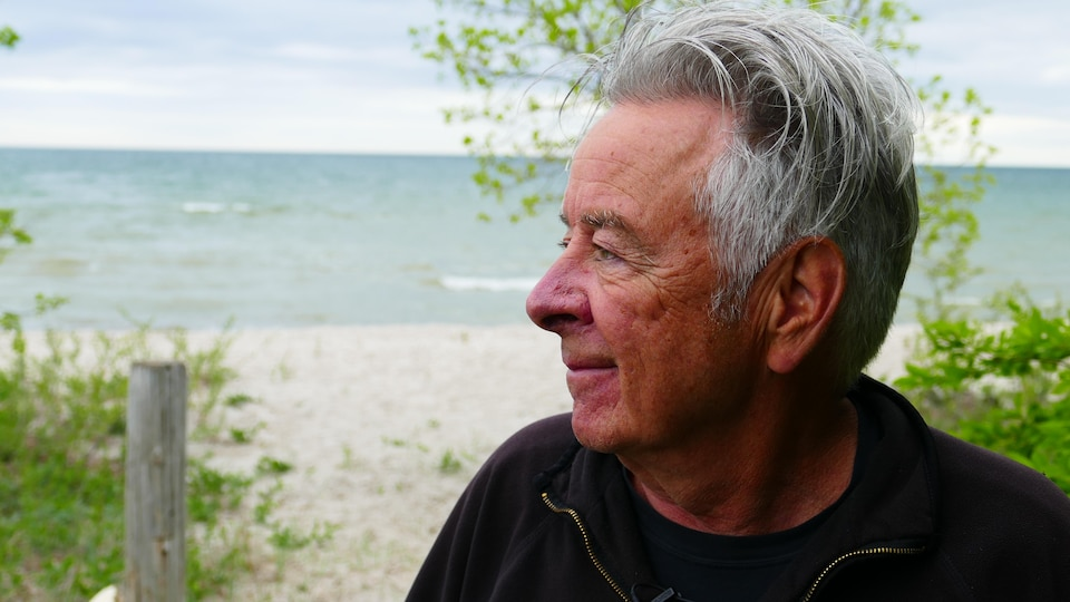 Un homme de profil, devant un lac.