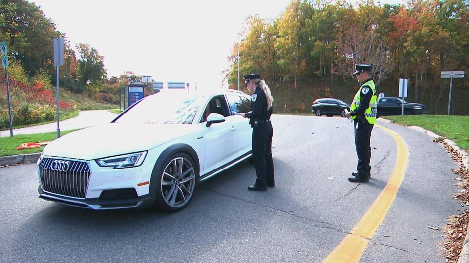 Une policière à pied s'entretient avec un automobiliste.