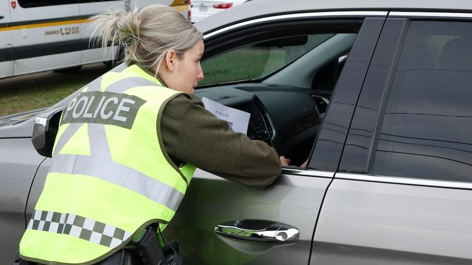 Une policière accotée sur la portière d'un automobiliste demande à ce dernier s'il a des informations sur les trois disparus.