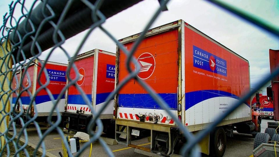 Des camions de Postes Canada dans un stationnement