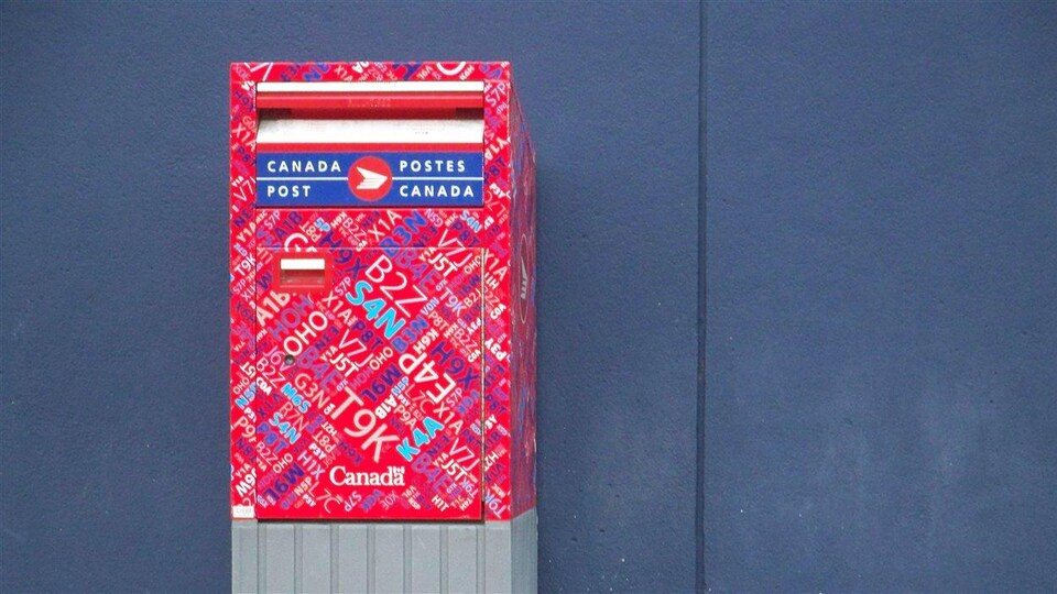Une boîte aux lettres de Postes Canada placée contre un mur dans le centre-ville de Vancouver.