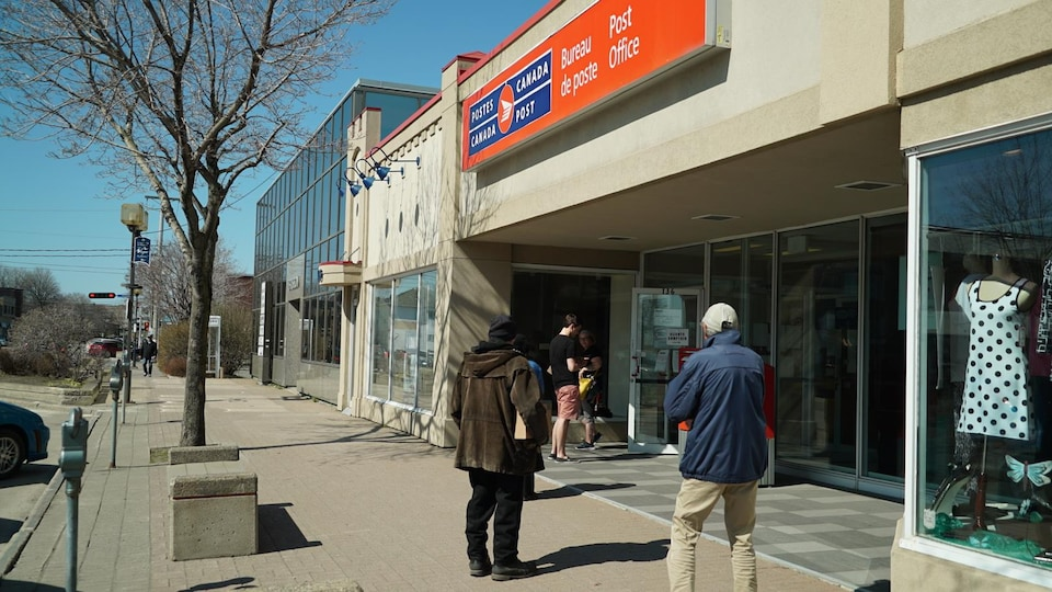 Une file de clients attendent devant le bureau de poste de Rimouski.