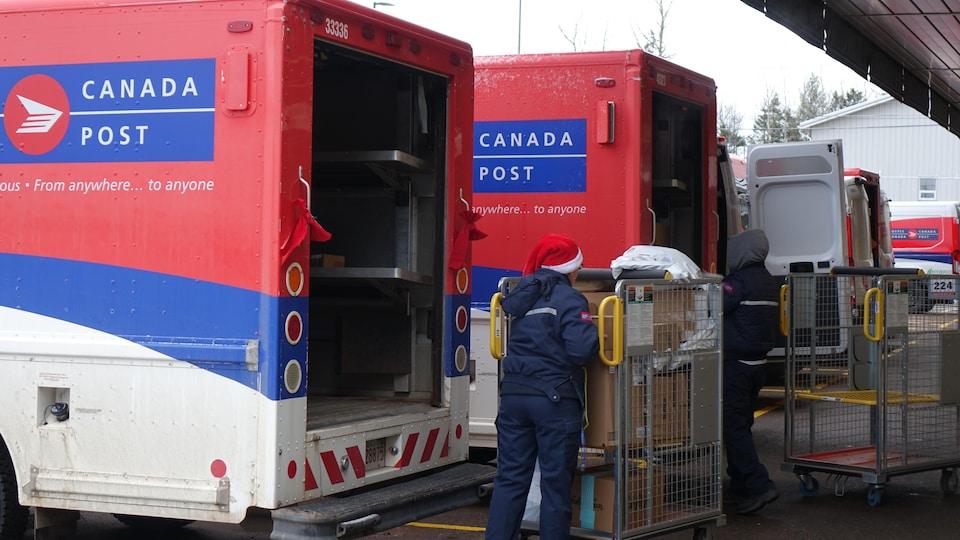 Une factrice remplit un camion de livraison de Postes Canada.