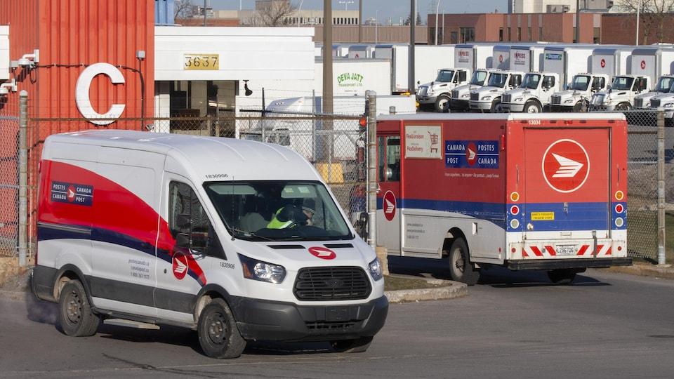 Des camions de livraison de Postes Canada sont stationnés.