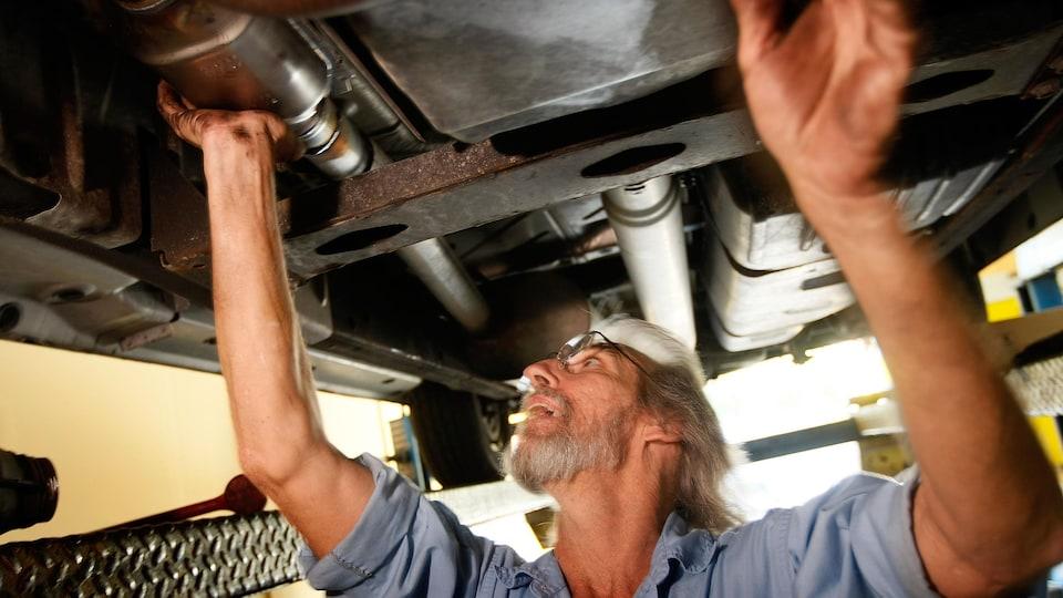 Un mécanicien remplace un pot catalytique sous une voiture.