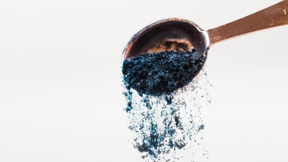 De la poudre bleue qui tombe d'une cuillère.