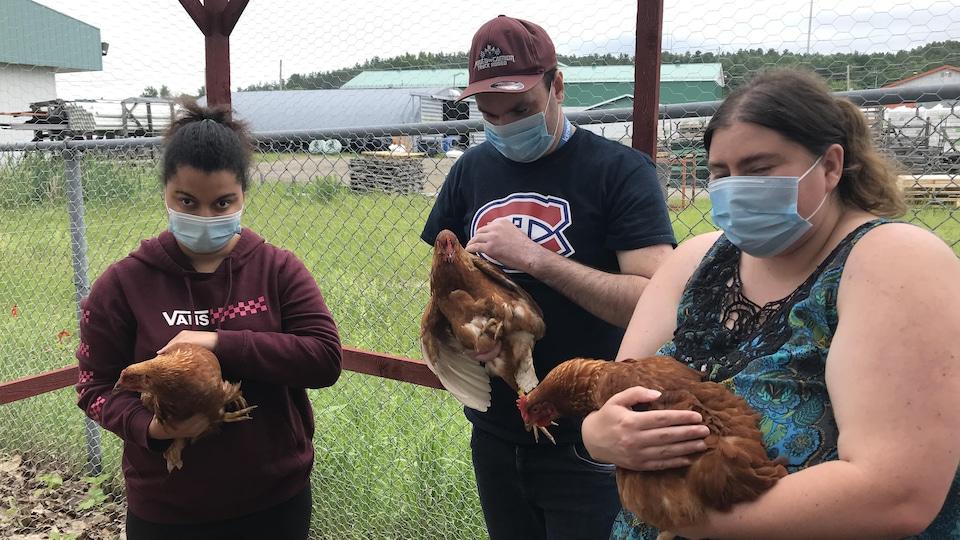Trois jeunes adultes handicapés tiennent chacun une poule.