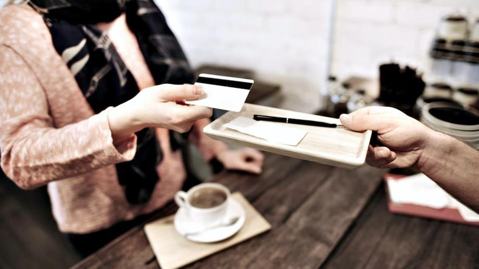 Une personne remettant une carte de crédit à un serveur lui tendant une facture
