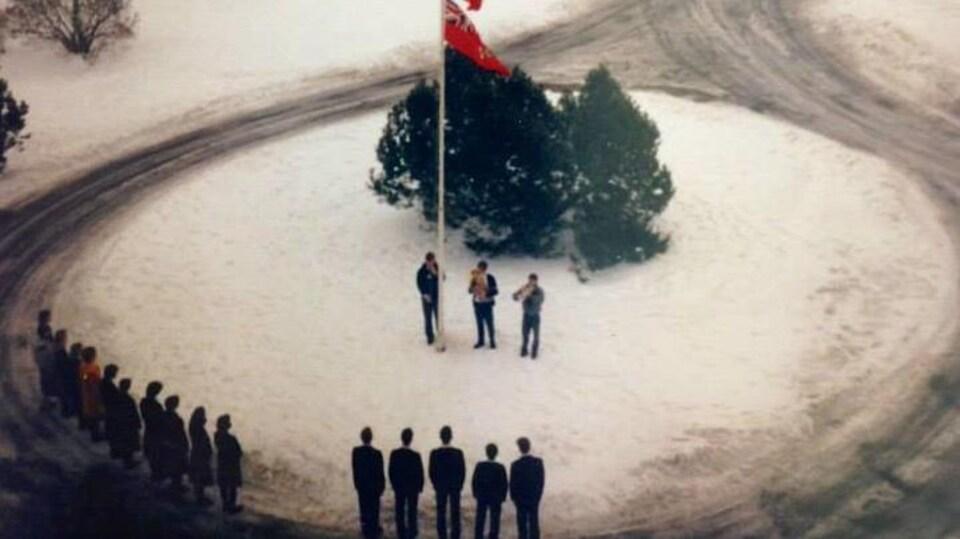 On voit une vieille photo de la levée traditionnelle des drapeaux au Collège Grenville.