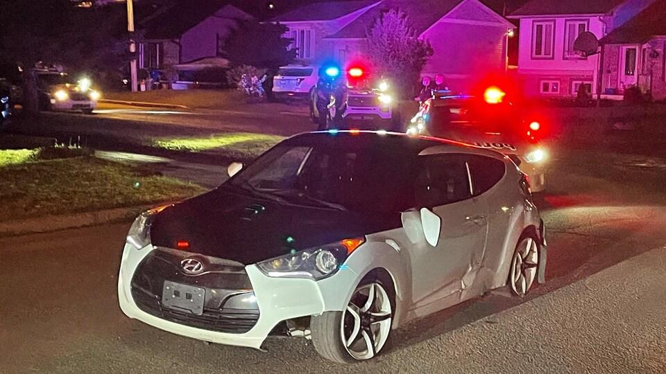 La voiture à deux portes est légèrement abîmée. Derrière, les gyrophares illuminent un secteur résidentiel la nuit et de nombreux agents de police sont sur place.
