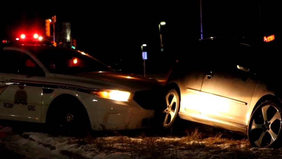 Photo prise de nuit d'une Jetta en bordure de la route, emboutie par une voiture de la GRC.