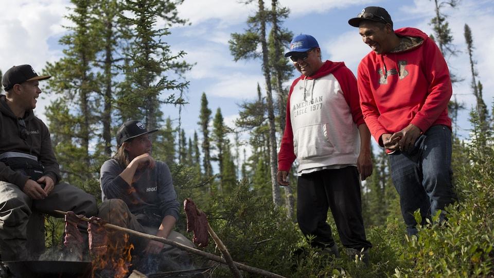 Quatre hommes plaisantent autour du feu en faisant griller de la viande.