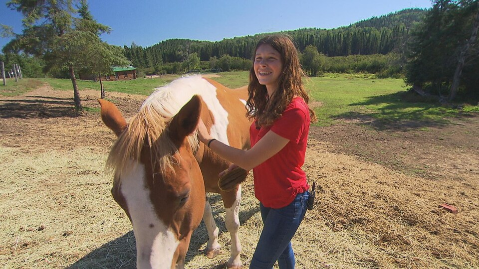 Myriam Caron, tout sourire, brosse un cheval à la robe brune et blanche.