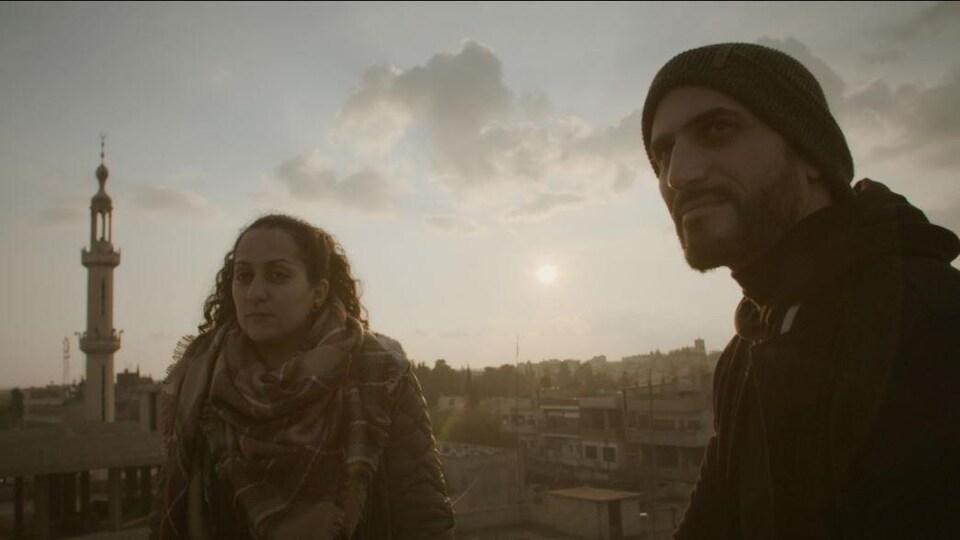 Une femme et un homme regardent hors champ. Le décor qui s'offre derrière est à quelque part en Syrie.
