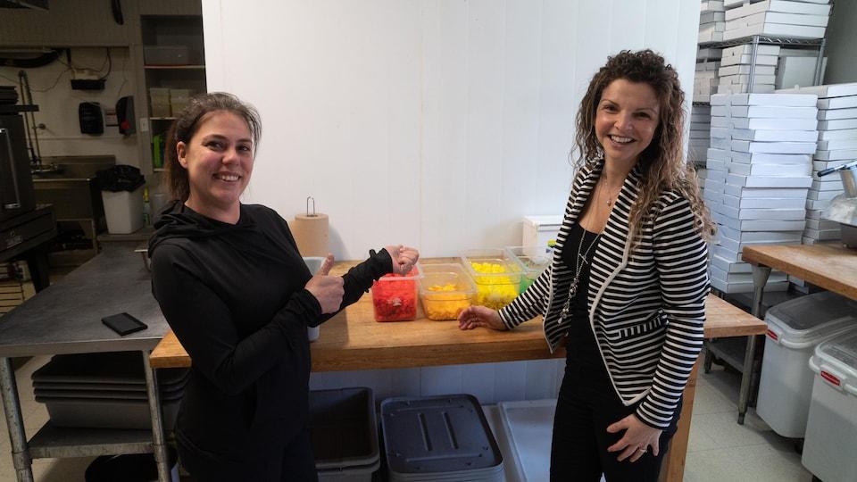 Sandra St-Jean et Jennifer Dumont posent devant leur fromage coloré.