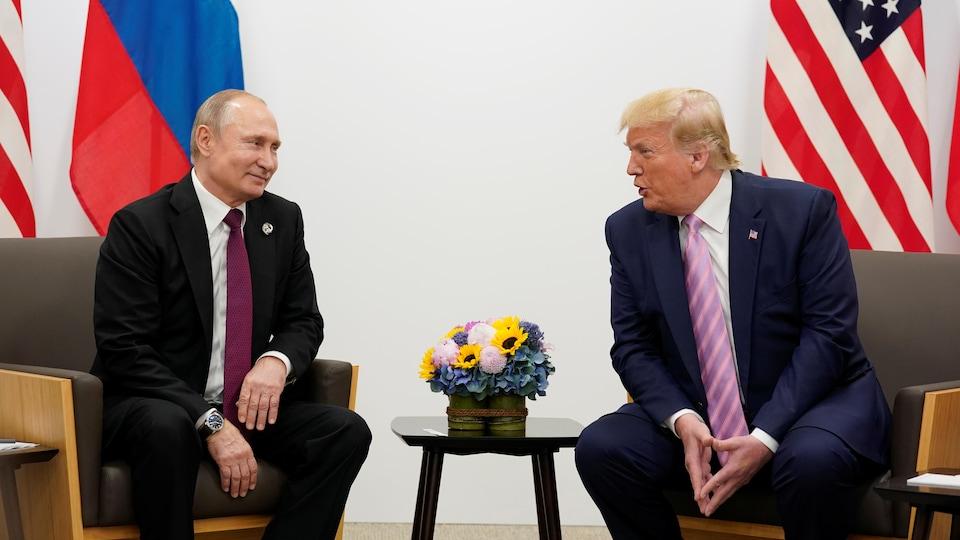 Vladimir Poutine et Donald Trump, légèrement penché vers son homologue, se sourient.