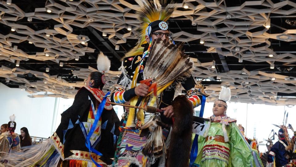 Un danseur de pow-wow avec des plumes devant son visage.