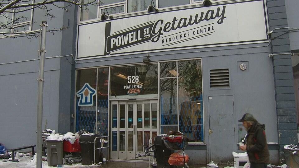 Un itinérant marche devant le centre Powell Getaway dans le Dowtown Eastside.