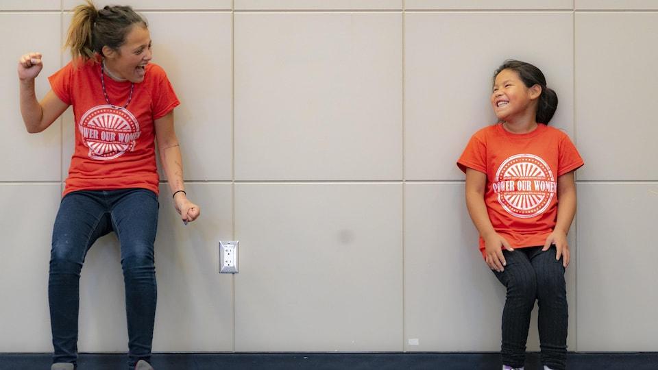 Deux jeunes filles lors d'un exercice contre le mur rigolent en se regardant.