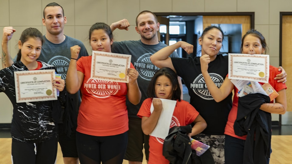 Un groupe de quatre jeune filles et une jeune femme et deux hommes posent avec des certificats en brandissant le poing.