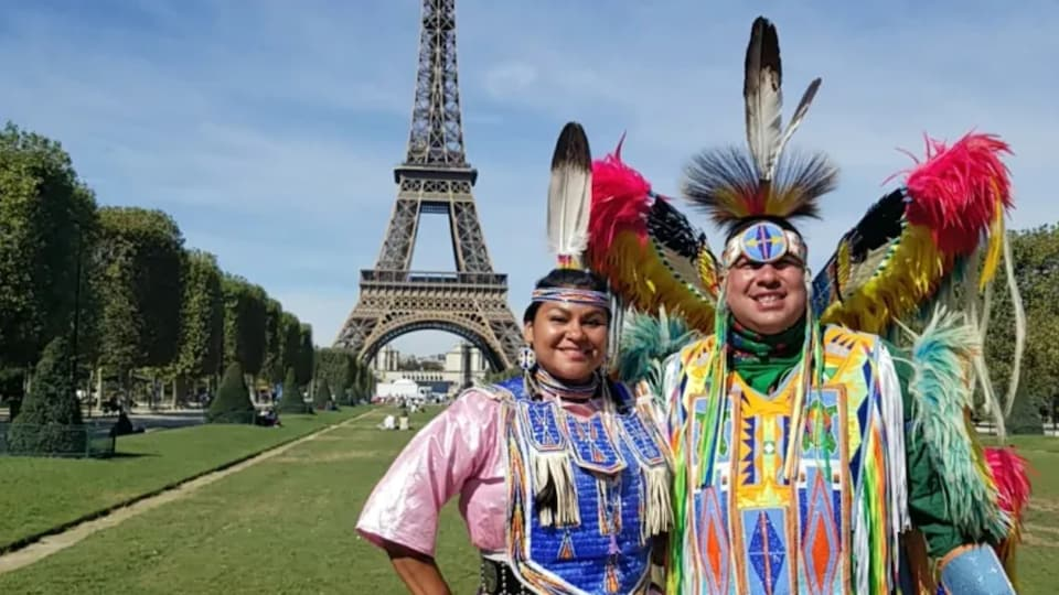 Deux personnes autochtones en tenue traditionnelle posent devant la tour Eiffel.