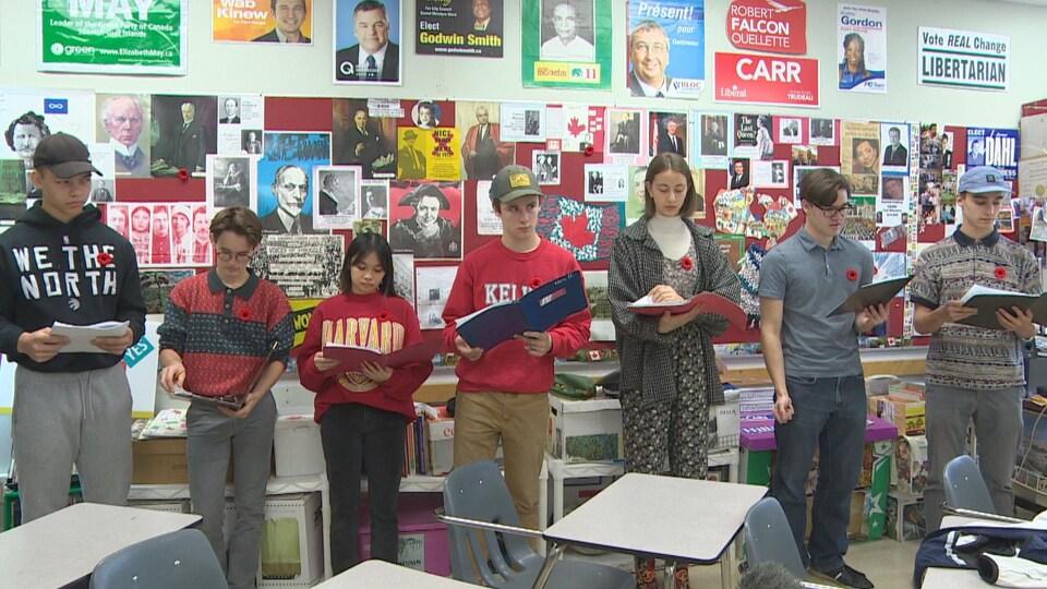 Alignés, deux adolescentes et cinq adolescents lisent des feuilles dans des cahiers.