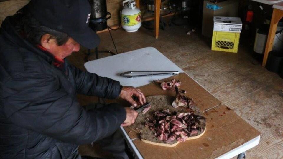 Un Autochtone coupe de la viande sur un plan de travail.