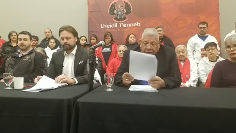 Les deux sont en costumes noirs, assis côte à côte à une table lisant la déclaration de poursuite civile contre Enbridge.