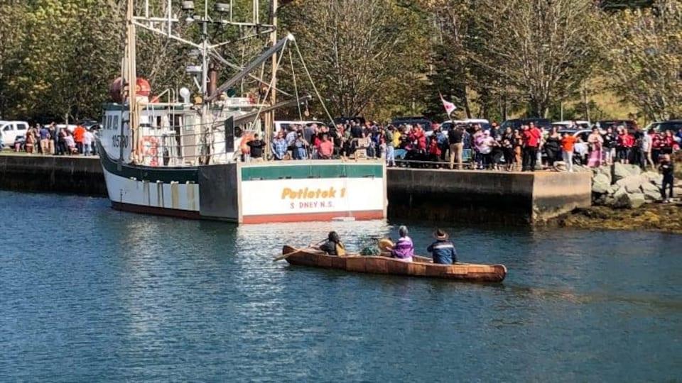 Un bateau de pêche est accosté à un quai, entouré de gens.