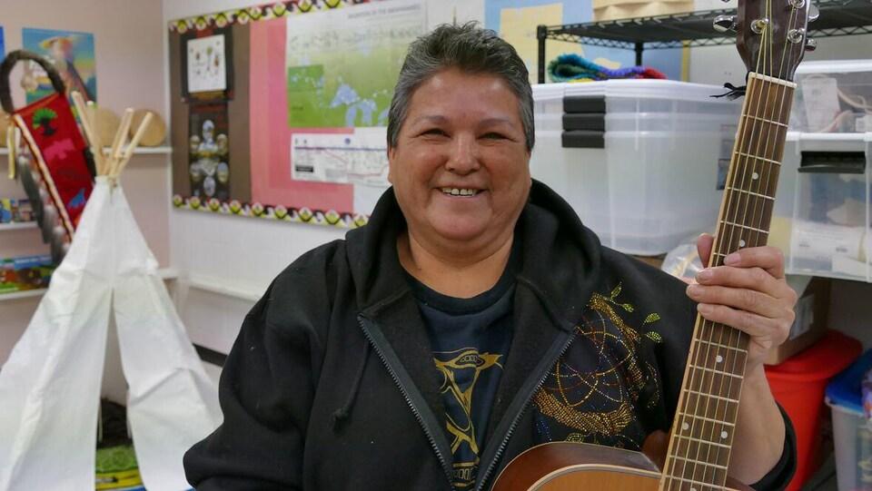 Une femme dans une salle qui tient une guitare dans les mains.