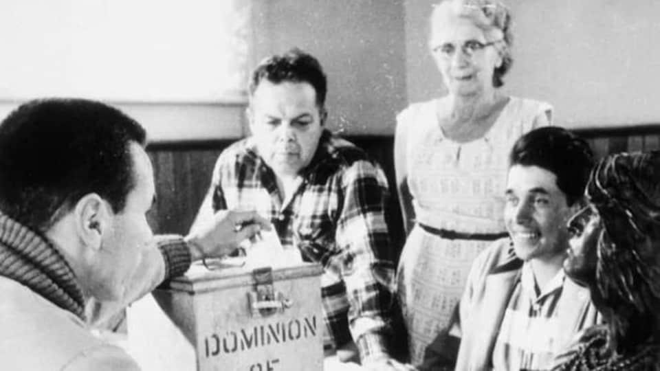 Photo en noir et blanc de quatre hommes et une femmes réunis autour d'une urne.