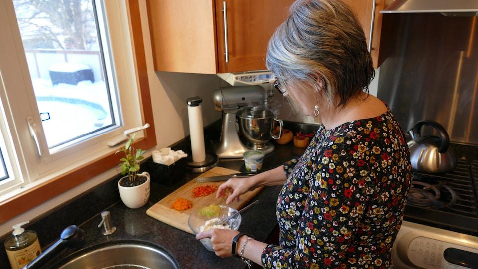 Une femme debout au comptoir de cuisine prépare un plat de fromage à la crème.