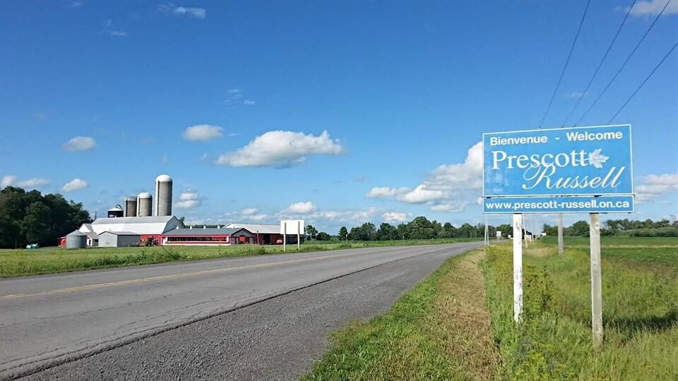 Une affiche le long d'une route devant une ferme